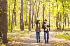 Amour, condition parentale, famille, saison et concept de personnes - les ajouter de sourire au bébé en automne se garent Photographie stock libre de droits