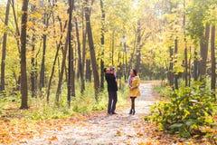 Amour, condition parentale, famille, saison et concept de personnes - les ajouter de sourire au bébé en automne se garent Photo stock