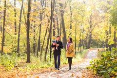 Amour, condition parentale, famille, saison et concept de personnes - les ajouter de sourire au bébé en automne se garent Photographie stock