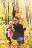 Amour, condition parentale, famille, saison et concept de personnes - les ajouter de sourire au bébé en automne se garent Images libres de droits