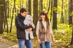 Amour, condition parentale, famille, saison et concept de personnes - les ajouter de sourire au bébé nouveau-né en automne se gar Photographie stock