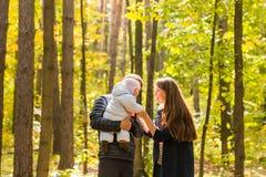 Amour, condition parentale, famille, saison et concept de personnes - les ajouter de sourire au bébé nouveau-né en automne se gar Image stock
