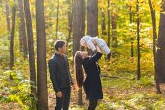 Amour, condition parentale, famille, saison et concept de personnes - les ajouter de sourire au bébé nouveau-né en automne se gar Photos stock