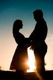 Amour - couple de coucher du soleil s'embrassant Images stock