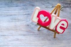 Amour décoratif d'inscription sur un petit chevalet en bois qui se tient dans le panneau de vintage Image libre de droits