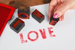 AMOUR d'impression de femme utilisant l'impression typographique en bois Photos libres de droits