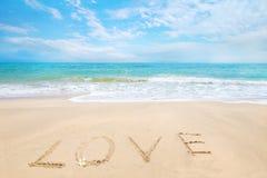 Amour d'inscription écrit sur la plage sablonneuse avec le ressac Photographie stock libre de droits