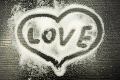 Amour d'inscription au coeur écrit avec un doigt sur le sucre renversé Photographie stock libre de droits