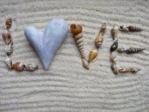 Amour d'inscription avec des coquilles sur le sable gris - foyer sélectif Photo libre de droits