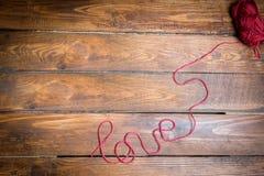 Amour d'inscription de fil rouge de laine sur un plancher en bois Images stock