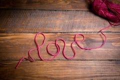Amour d'inscription de fil rouge de laine sur un plancher en bois Photographie stock