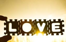 Amour d'inscription des puzzles contre le coucher du soleil Photo libre de droits