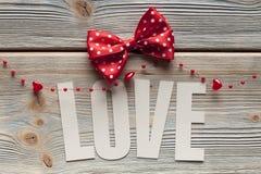 Amour d'inscription et un arc rouge sur le fond en bois Images stock