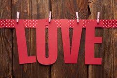 Amour d'inscription et un ruban rouge sur le fond en bois Photographie stock