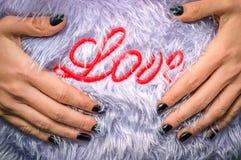 Amour d'inscription sur une serviette éponge, les mains du ` s de fille Images libres de droits