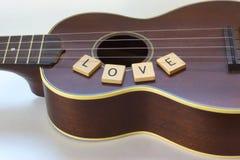 Amour d'ukulélé avec les tuiles carrées de lettre sur le blanc Image libre de droits
