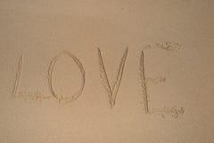 Amour dans le sable avec le coeur en pierre Images stock