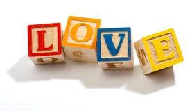 Amour dans les blocs en bois de lettre sur le fond blanc Images stock