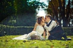 Amour dans les rayons du soleil - le marié embrasse une jeune mariée tandis qu'ils se reposent dessus Photo libre de droits