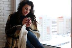 Amour de attente de belle fille se reposant sur le wrappe de rebord de fenêtre Photographie stock