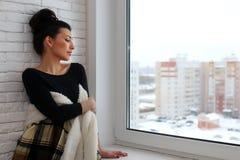 Amour de attente de fille se reposant sur le rebord de fenêtre enveloppé dans un bla Image stock