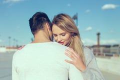 Amour de chuchotement de jeune homme à la femme blonde dehors Photographie stock
