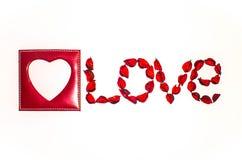 Amour de coeur et de mot présenté des fleurs artificielles sur un fond blanc Photos libres de droits