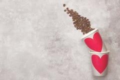 Amour de concept au café Les tasses de papier grises pour des boissons avec le rouge entendent Photographie stock