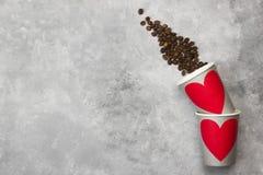 Amour de concept au café Les tasses de papier grises pour des boissons avec le rouge entendent Photos stock