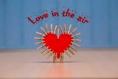 Amour de ` dans la carte de ` d'air avec le coeur de papier rouge sur la table Images stock