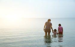Amour de famille marchant sur l'océan Photos stock