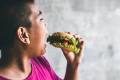 Amour de garçons pour manger l'hamburger Photo libre de droits