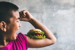 Amour de garçons pour manger l'hamburger Photographie stock libre de droits