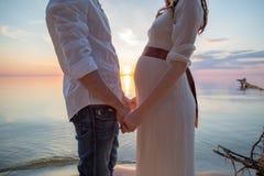Amour de l'homme et de femme enceinte : deux mains au coucher du soleil sur la plage Photographie stock libre de droits