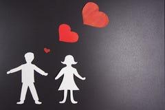 Amour de l'homme et de femme Silhouettes de papier des amants avec les coeurs rouges au-dessus de eux sur le fond noir Photo stock