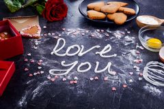Amour de lettrage de crème de meringue de vue supérieure vous sur le fond en pierre noir avec les ingrédients, la fleur, le boîte Photographie stock