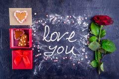 Amour de lettrage de crème de meringue de vue supérieure vous sur le fond en pierre noir avec les ingrédients, la fleur, le boîte Image stock