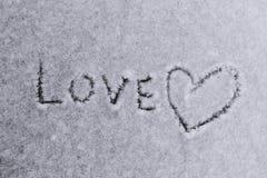 Amour de mot écrit et un symbole de coeur sur un fond neigeux blanc Photographie stock