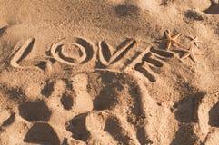 Amour de mot écrit sur le sable Photos libres de droits