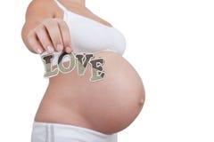 Amour de mot de prise de femme enceinte dans des mains Image stock