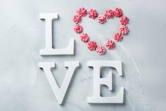 Amour de mot des textes de vacances de jour de valentines avec le coeur rose de meringue Photos stock