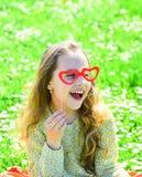 Amour de premier concept de vue Enfant posant avec les lunettes en forme de coeur de carton La fille s'assied sur l'herbe au gras Photo libre de droits
