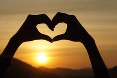 Amour de sentiment de geste de main de silhouette pendant le coucher du soleil Photos libres de droits