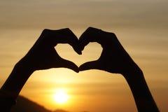 Amour de sentiment de geste de main de silhouette pendant le coucher du soleil Image stock
