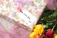 Amour de ` vous étiquette de ` sur le présent enveloppé à côté des roses Image stock