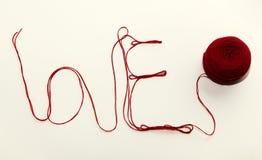 Amour de Word écrit avec le fil rouge de laine au-dessus du backg blanc Photo libre de droits