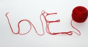 Amour de Word écrit avec le fil rouge de laine d'isolement au-dessus du backg blanc Photos stock