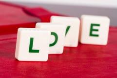 Amour de Word avec des lettres sur le fond rouge Photos stock