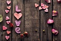 Amour de Word avec les pétales de rose et le petit coeur Photographie stock