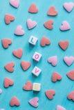 Amour de Word construit des cubes empilés en lettre Sugar Candy Sprinkles Scattered rouge-rose sur le fond bleu-clair valentine Photographie stock libre de droits